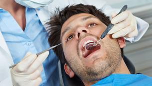 Zahnärztin mit Sonde und Spiegel am Patient